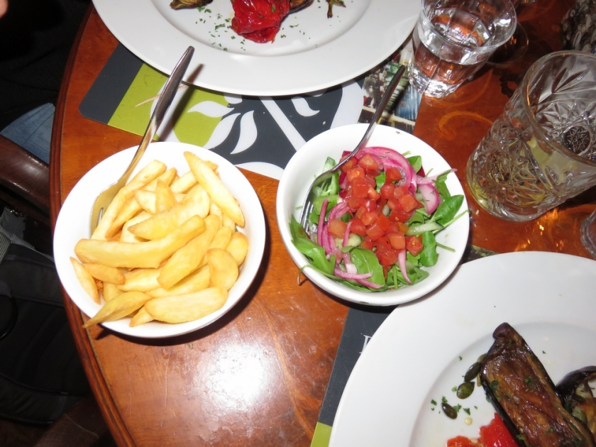 and potato wedges and a salad with cubed tomatos