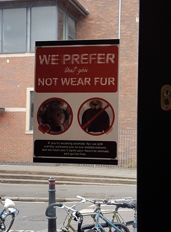 Sticket saying: we prefer that you not wear fur, with two images; one of an animal, with a heart next to it, one of a fur coat, with a line through it.