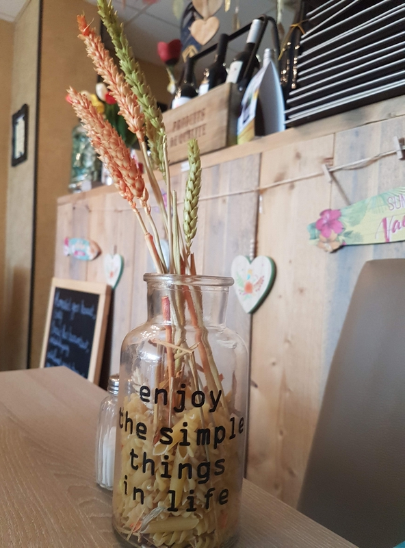 Glass jar with dried wheat. Counter in the back. Text on jar reads: Enjoy the simple things in life.