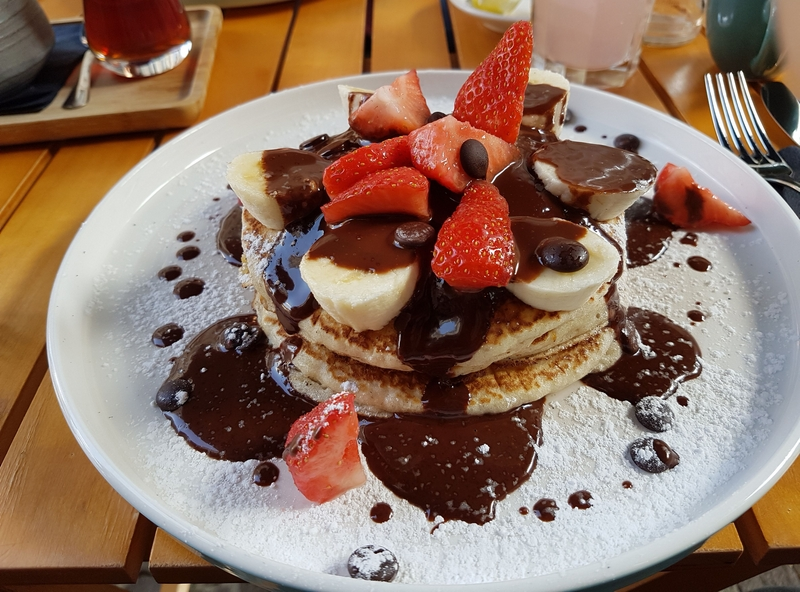 stack of pancakes covered in fruit and chocolate sauce