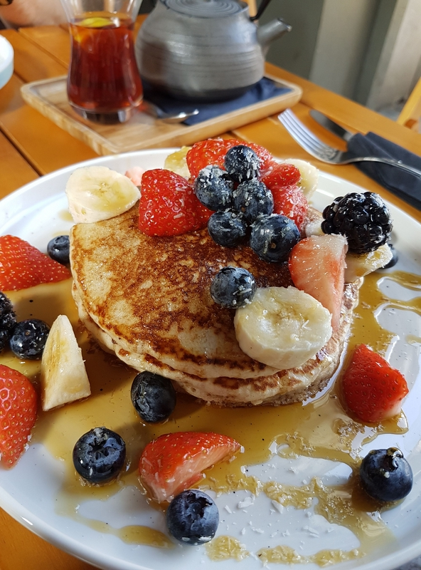 stack of pancakes covered in fruit and maple syrup